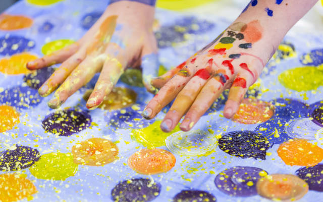 Student's hands covered in colourful paint