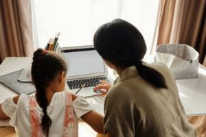 Mother helping daughter with online learning at a laptop